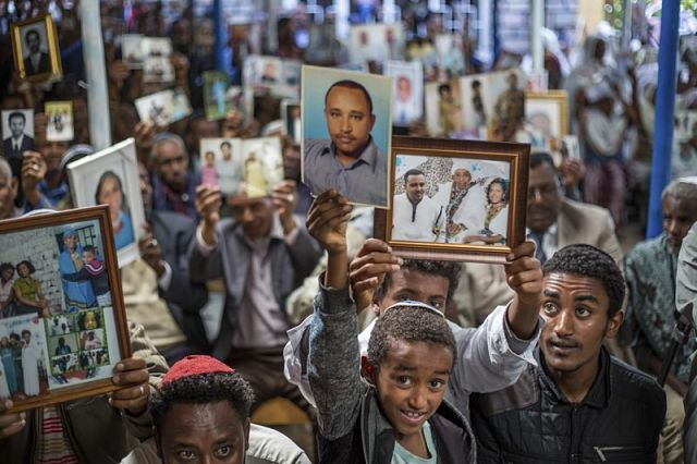 Members of Ethiopia's Jewish community hold pictures of their relatives in  Israel, during a solidarity event at the synagogue in Addis Ababa, ...